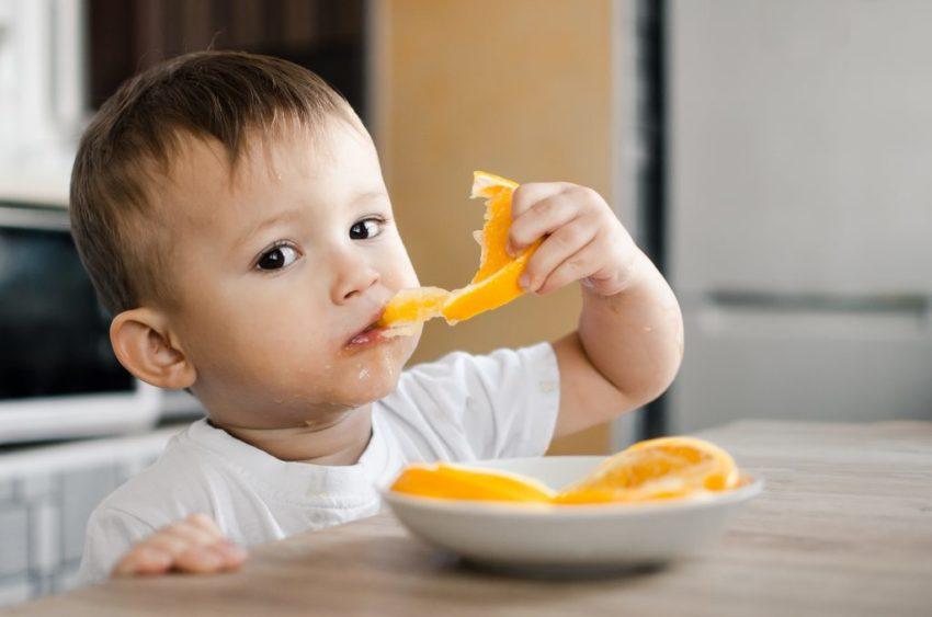 Ребенок кушает апельсин
